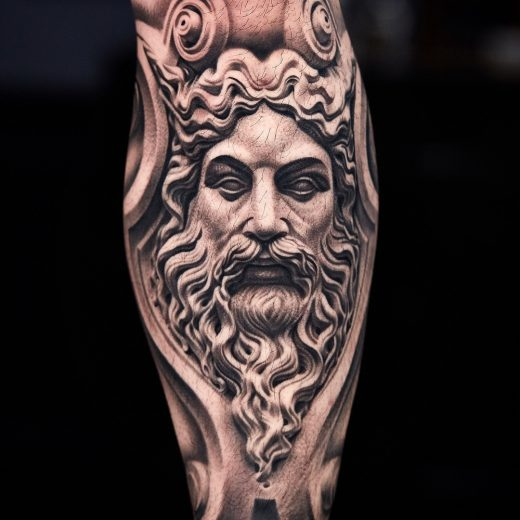 A photo of black and grey statue tattoo on the shin by artist Kiljun at Seoul Ink Tattoo Studio.